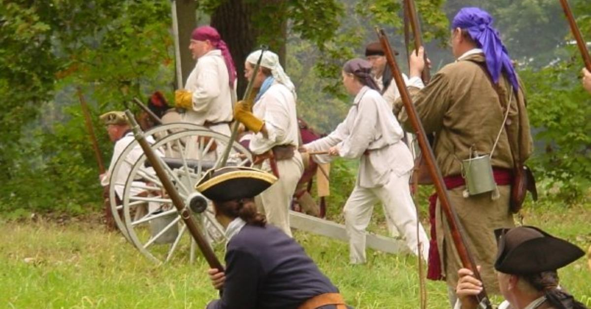 reenactors with muskets standing near a cannon