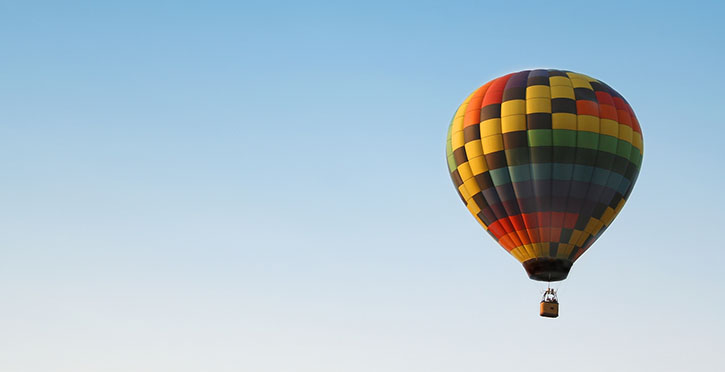 Hot air baloon with colorful square pattern rising in the air