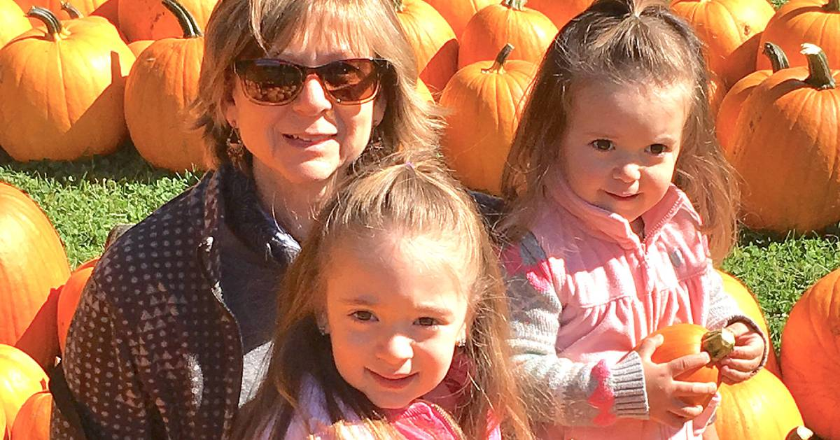 woman and two girls with pumpkins