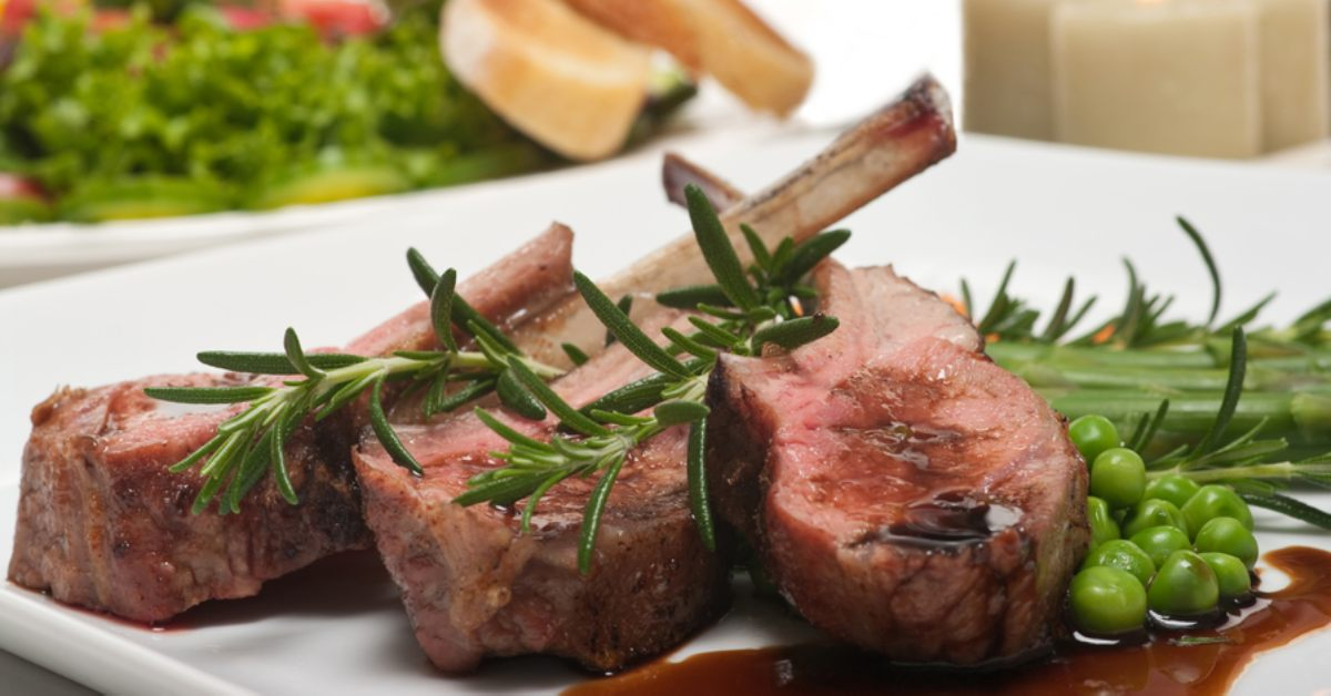 lamb chops and rosemary on a white plate