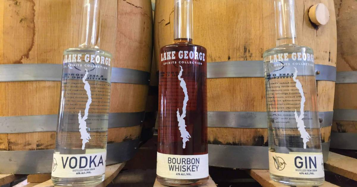 three liquor bottles in front of barrels