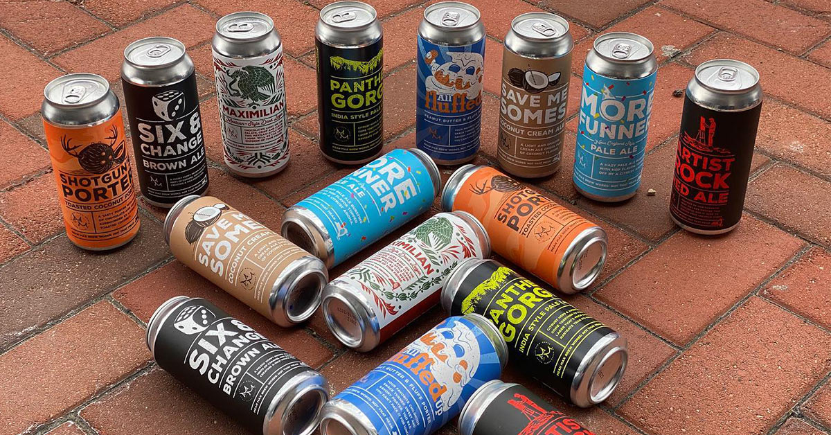 cans of mean max beer on a brick sidewalk