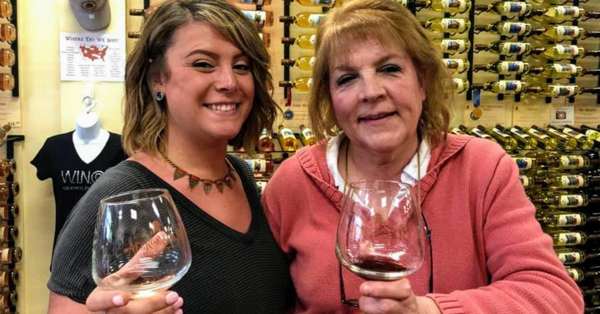 mother and daughter holding up wine glasses