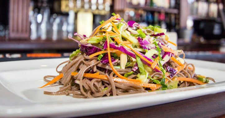 asian noodle salad topped with cabbage slaw