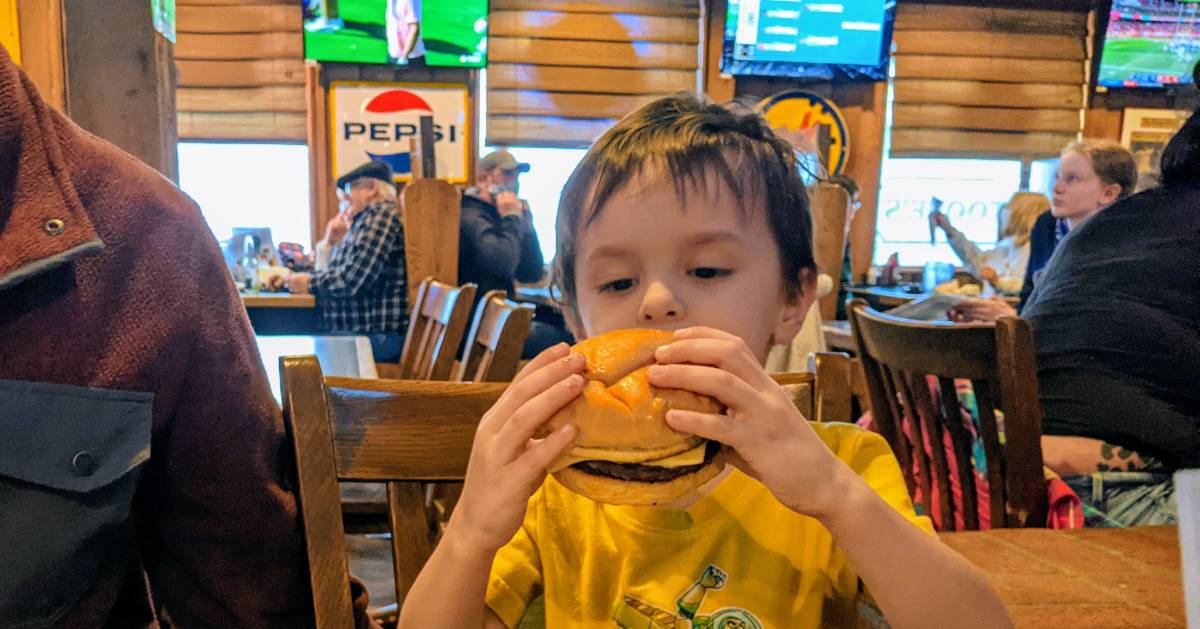 kid in restaurant with a cheeseburger