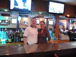 Man and woman posing behind bar
