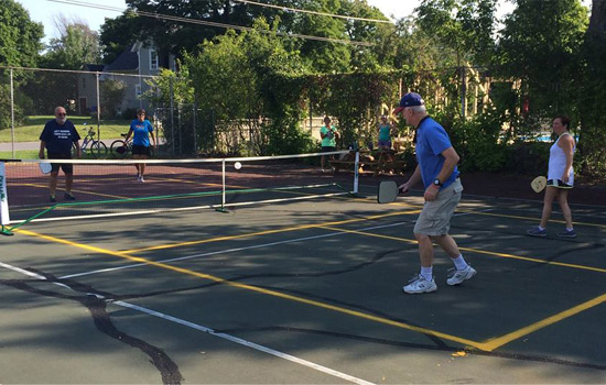 a group of four playing pickleball on an outdoor court