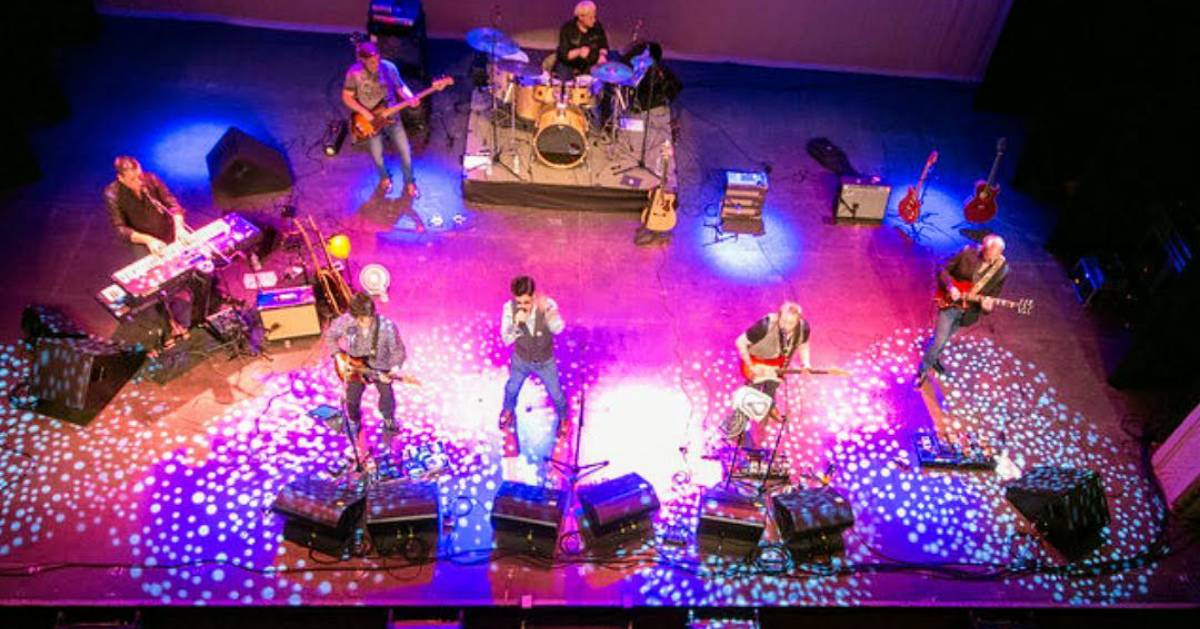 pink and blue lights on a stage with band performing