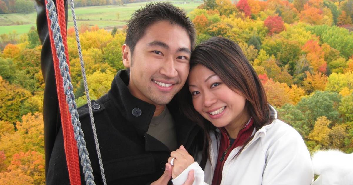 an engaged couple on hot air balloon showing off the ring