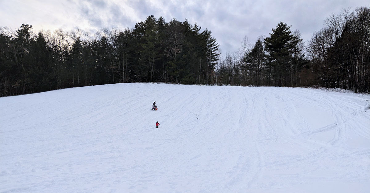 father and son climbing up the tubing hill at lake george recreation center
