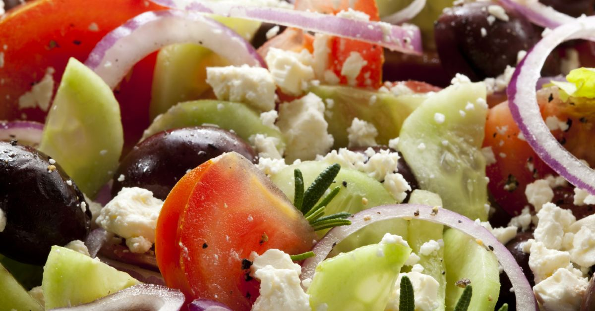 tomatoes, red onions, cucumbers, and feta cheese in a salad