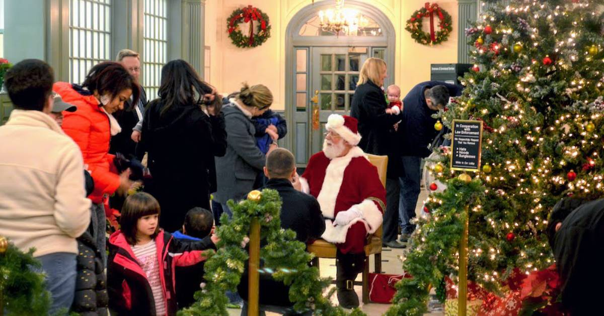 Santa in hotel with people waiting to see him