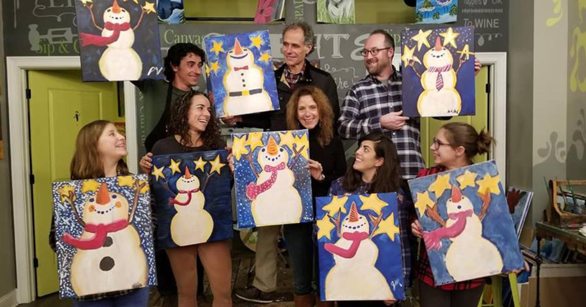 group of people holding up paintings