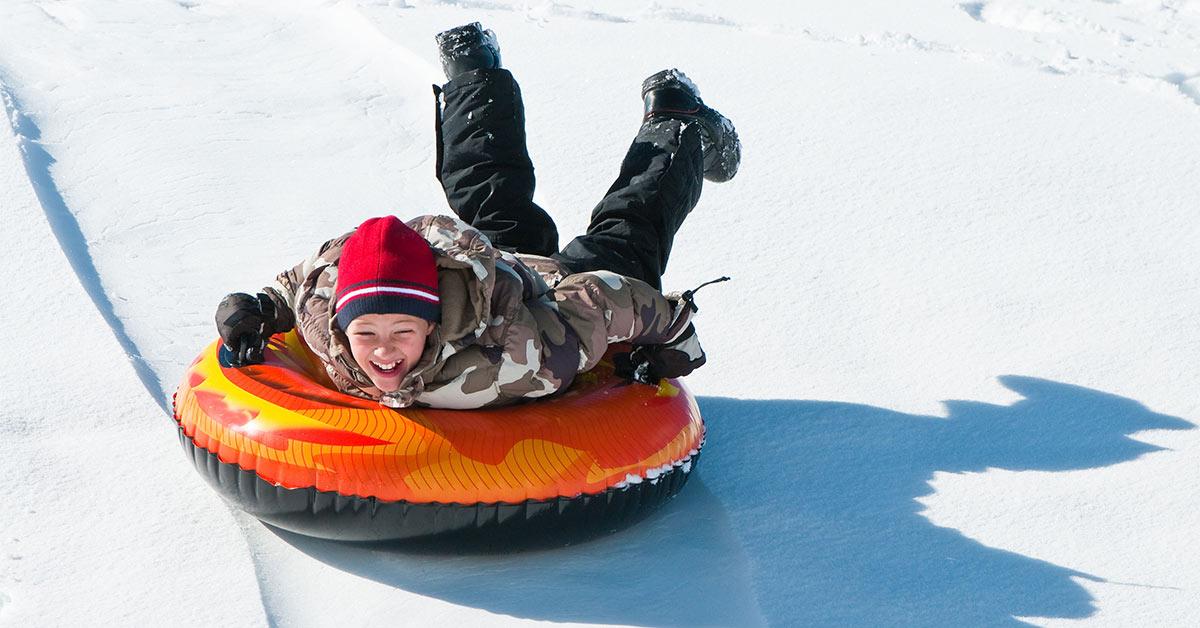 boy on an orange snow tube