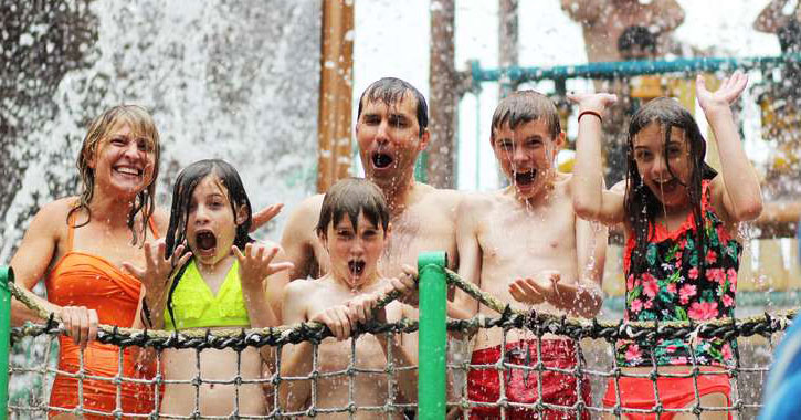 a family getting soaked at a water park