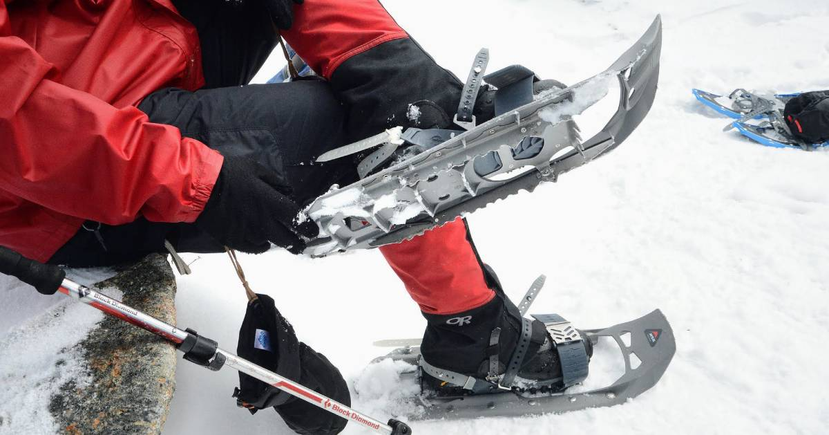 close up of person strapping on snowshoes