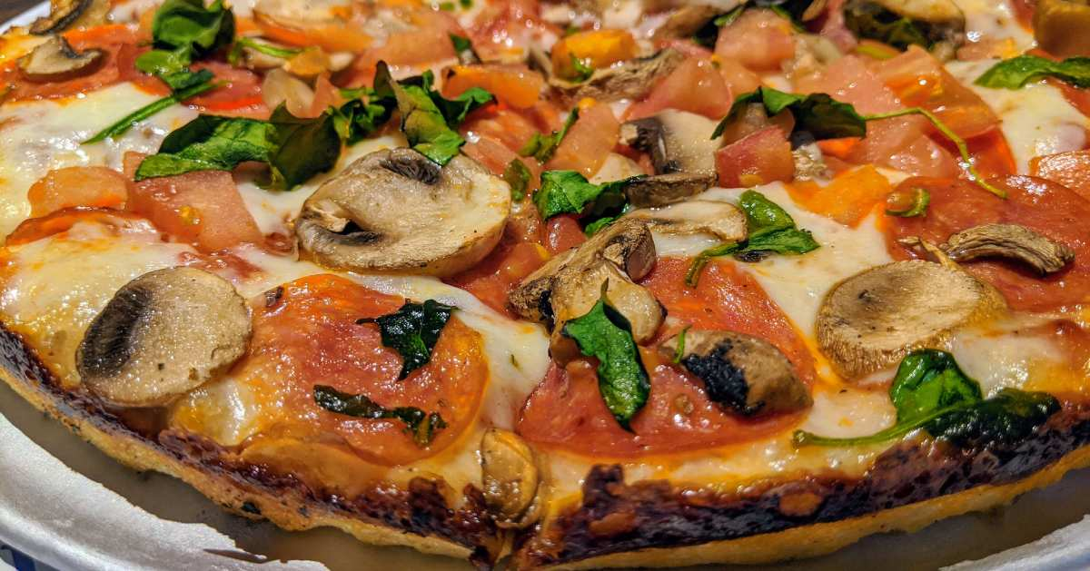 view of veggie pizza with tomatoes, basil, and mushrooms