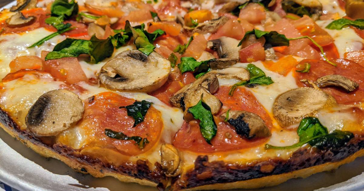 pizza with mushrooms, spinach, tomatoes, and pepperoni