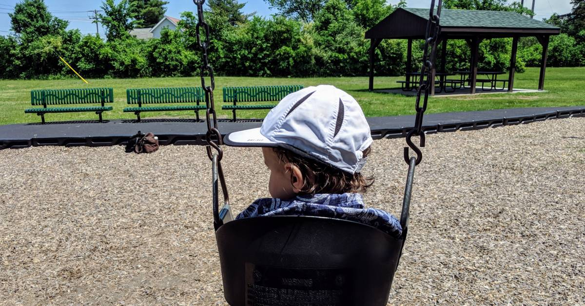 toddler on swing, view from the back