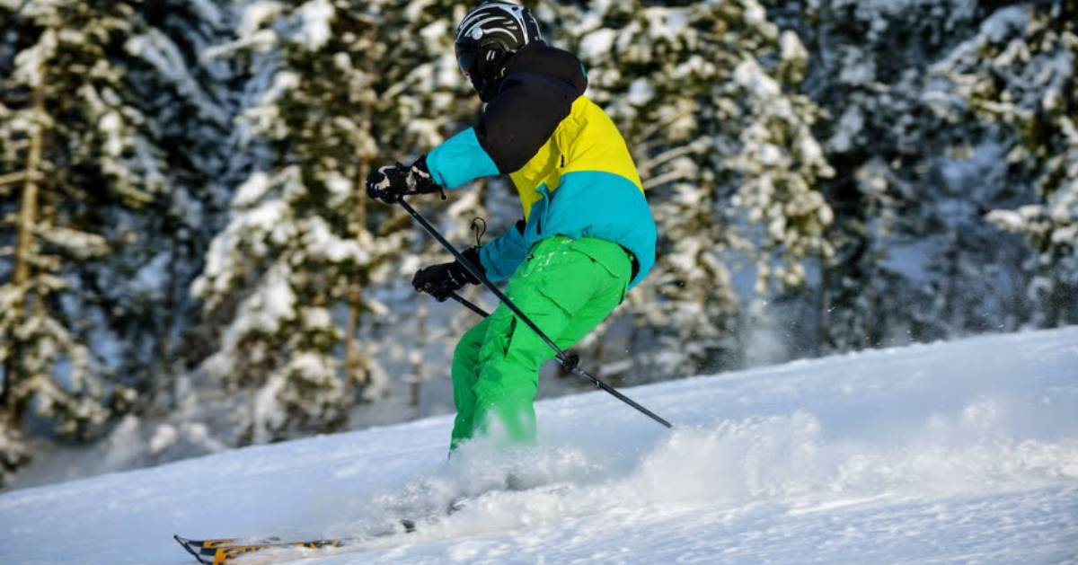skier on mountain in bright clothes