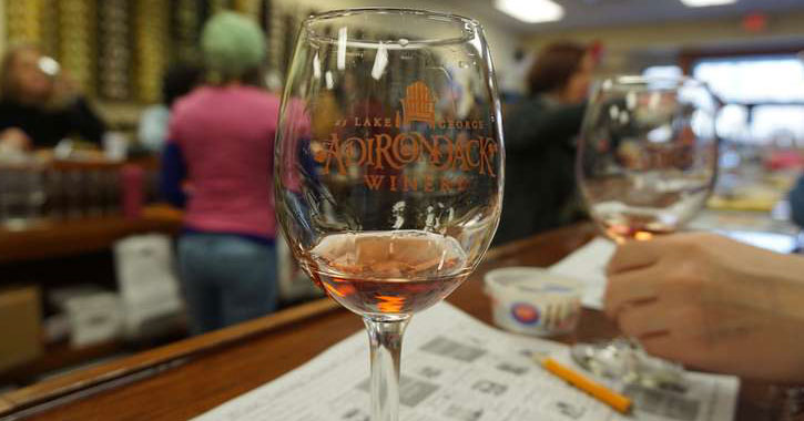 a wine glass that says Adirondack Winery on a bar