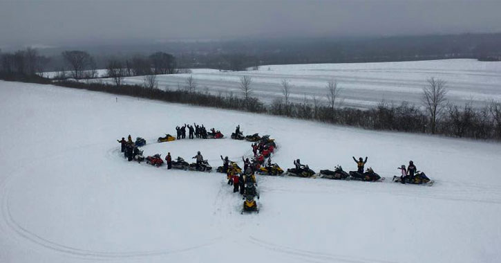 snowmobiles lined up in the shape of a cancer ribbon