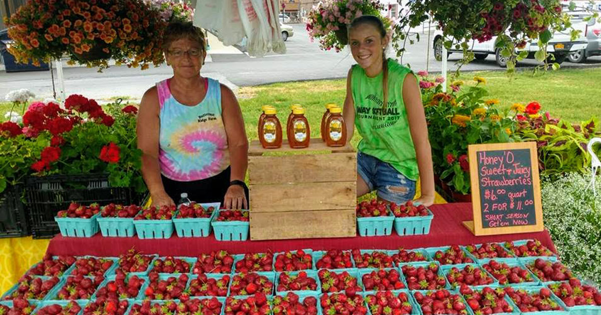 two women at farm stand with strawberries
