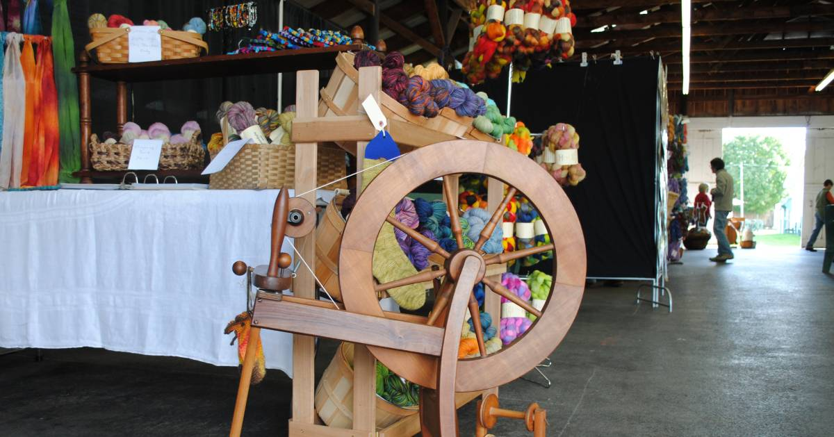 wool vendor at festival, spinning wheel
