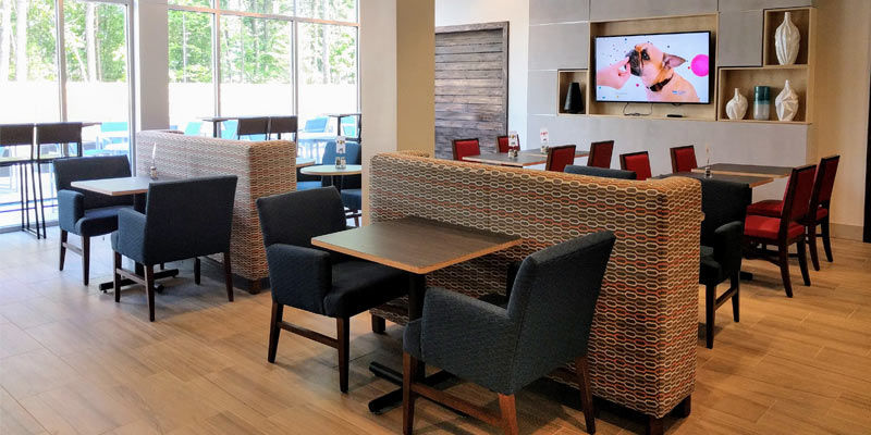 the breakfast/lobby area of the hotel with a TV on with a small dog on it, outside seating is visible through glass windows