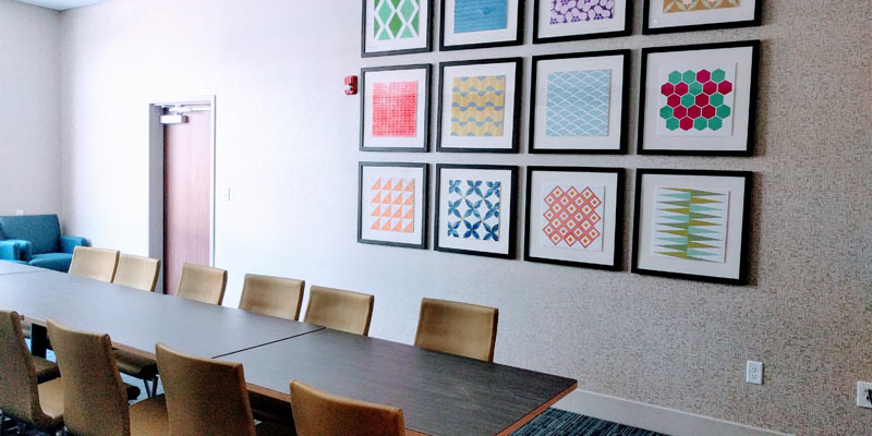 a long table with chairs with colorful artwork on the wall
