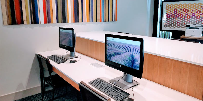 two computers in the hotel lobby with funky artwork on the wall