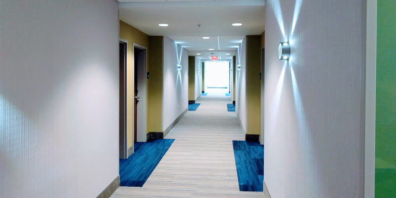the hallway of a hotel with blue carpets in front of the doors and funky lights on the walls