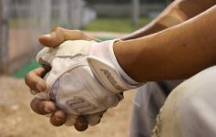a close up of the hands of a baseball player on the bench, he has at least one white glove on
