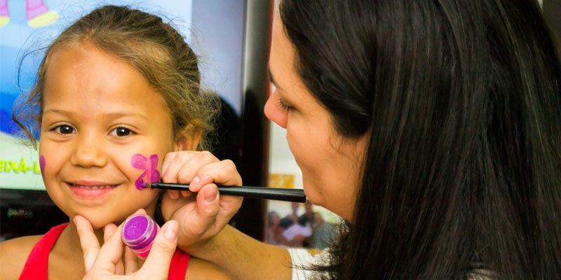 a little girl getting her face painted with purple flowers on each cheek