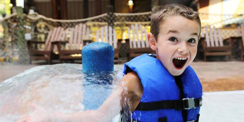 a little boy with a blue lifejacket plays in Great Escape's water park with a huge grin