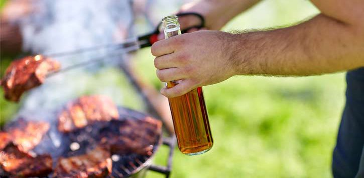 close up of man holding a beer while barbecuing
