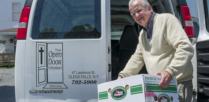 elderly guy with box about to load up in van with Open Door Mission logo