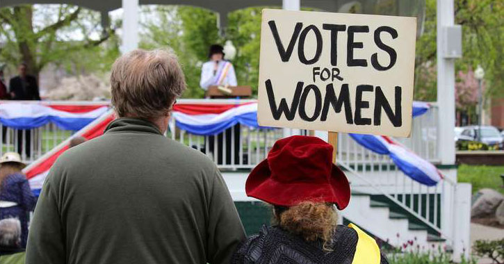 part of a crowd with someone holding a sign saying Votes for Women