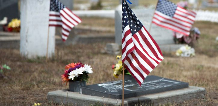 flags by graves in the cemetery