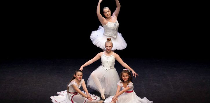 four young ballerinas posing