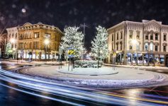 Traffic circle in downton Glens Falls at night during the winter with lights and snow