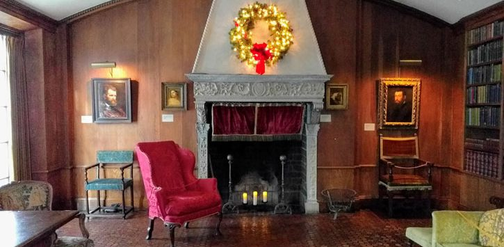 a room in the Hyde House with a fireplace, wreath hanging, and artwork