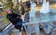 a man playing piano at an ice bar