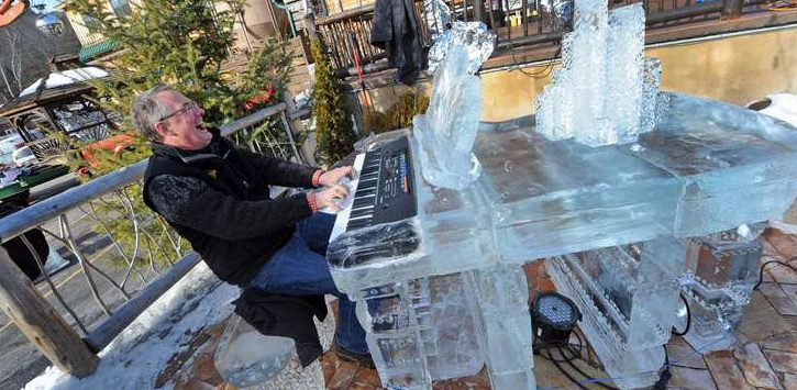 a man playing piano at an ice bar