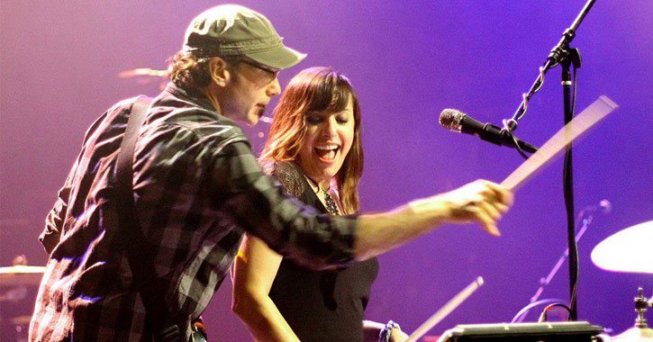 a man and woman performing music on stage, purple background