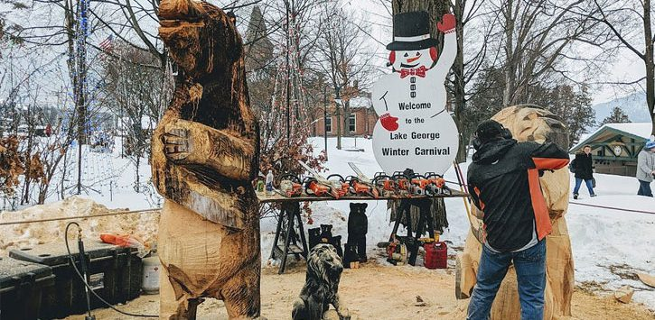 a man doing a chainsaw carving at the Lake George Winter Carnival