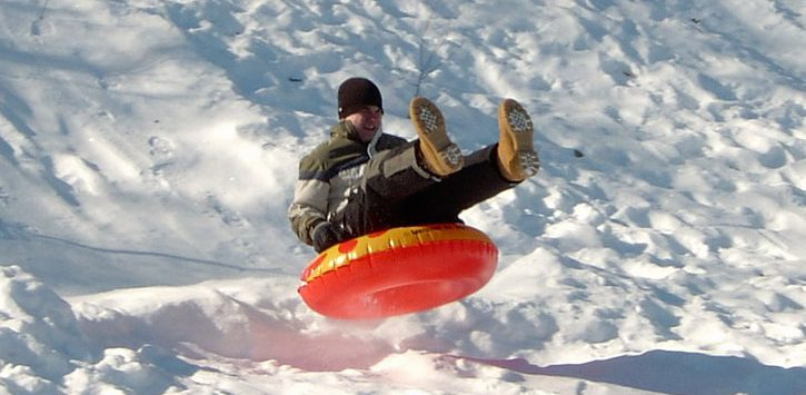 a guy sledding down a hill in an orange tube