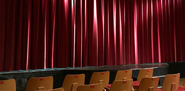 empty seats in a theater with red curtain