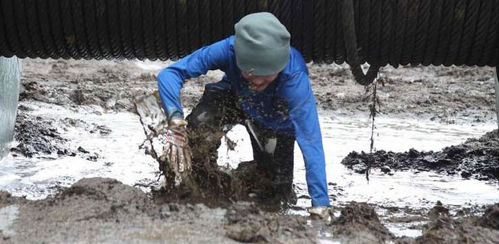 person struggling through mud