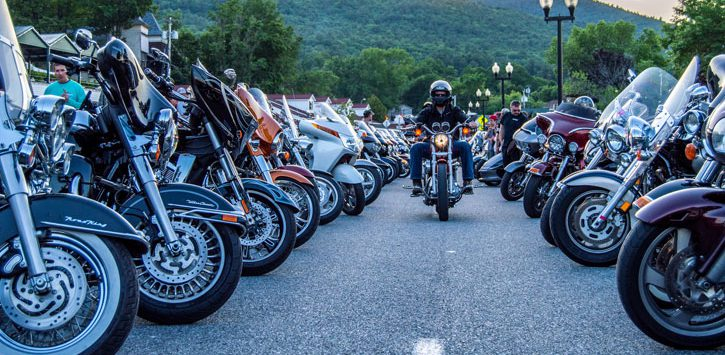 row of motorcycles in Americade, biker moving down the middle